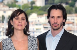 "US actor Keanu Reeves and Canadian-born actress Carrie-Anne Moss pose for photographers on a terrace of the Palais des festivals during the photocall for ""Matrix Reloaded"" directed by the Wachowski brothers during the 56th Cannes film festival on 15 May 2003. - Sci-fi franchise ""The Matrix"" will return for a fourth film with Keanu Reeves reprising his role as kung fu-kicking, shades-wearing hero Neo, studio Warner Bros said Tuesday. Lana Wachowski will helm the project, returning to write, direct and produce the latest installment of the hugely popular series about humans trapped in a virtual reality by machines, which has netted more than $1.6 billion worldwide. (Photo by FRANCOIS GUILLOT / AFP) / ALTERNATIVE CROP"