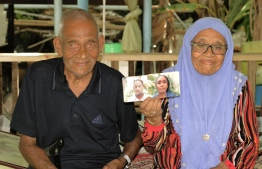Abdulla Rafeeq and Aisaadhy hold up a photograph of themselves from their youth. PHOTO: HAWWA AMAANY ABDULLA / THE EDITION