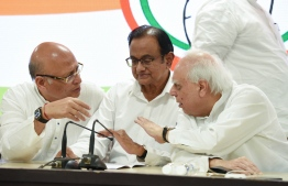 India's former finance minister and Congress party leader P. Chidambaram (C) talks with other leaders Kapil Sibal (R) and Abhishek Manu Singhvi during a press conference at the party headquarters in New Delhi on August 21, 2019. - High drama unfolded in Delhi late on August 21 as officers from India's equivalent of the FBI scaled the walls of former finance minister Chidambaram's home to arrest him on corruption charges, local media reported. (Photo by STR / AFP)