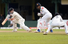 New Zealand's cricketer Henry Nicholls (L) watches as Sri Lankan cricketer Dhananjaya de Silva (R) takes a catch to dismiss him during the third day of the final cricket Test match between Sri Lanka and New Zealand at P. Sara Oval stadium in Colombo on August 24, 2019. (Photo by LAKRUWAN WANNIARACHCHI / AFP)