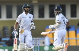 Virat Kohli (L) and Ajinkya Rahane (R) of India 100 partnership during day 3 of the 1st Test between West Indies and India at Vivian Richards Cricket Stadium in North Sound, Antigua and Barbuda, on August 24, 2019. (Photo by Randy Brooks / AFP)
