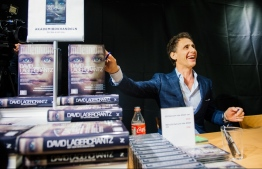 "(FILES) In this file photo taken on August 28, 2015, the author of the fourth novel in the Millennium series of crime novels, originally by Stieg Larsson, The Girl in the Spider's Web, Swedish journalist and best-selling author, David Lagercrantz, signs the books for first buyers during a midnight sell at a local book store in Stockholm. - In ""The Girl Who Lived Twice"", Swedish crime writer Stieg Larsson's antiheroine Lisbeth Salander is back for the final instalment of the ""Millennium"" saga, which is hitting shelves in 47 countries. (Photo by Jonathan NACKSTRAND / AFP)"