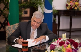 Sri Lanka Prime Minister Ranil Wickremesinghe signs the Guest Book at the Maldivian parliament. PHOTO/MAJILIS
