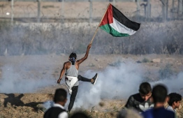 A protester raises a Palestinian flag during clashes with Israeli forces across the border following a demonstration east of Bureij in the central Gaza Strip on September 6, 2019. - Two Palestinian teenagers were killed by Israeli fire in renewed clashes along the Gaza border, the health ministry in the Hamas-run enclave said. (Photo by MAHMUD HAMS / AFP)