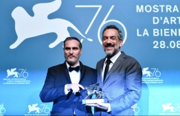 "US director Todd Phillips (R), flanked by US actor Joaquin Phoenix, holds the Golden Lion award for Best Film he received for the movie ""Joker"" during the awards ceremony winners photocall of the 76th Venice Film Festival on September 7, 2019 at Venice Lido.  Alberto PIZZOLI / AFP"