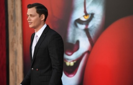 """(FILES) In this file photo taken on August 26, 2019 Swedish actor Bill Skarsgard arrives for the World premiere of """"It Chapter Two"""" at the Regency Village theatre in Westwood, California. - Pennywise, the murderous clown who lurks in sewers and feasts on terrified children, is perhaps the most evil creation to ever emerge from the warped mind of Stephen King. But the director of the record-breaking, two-part film adaptation of """"It"""" has controversially claimed that King's horrifying invention shares a lot in common with a real-life figure -- President Donald Trump. (Photo by Robyn Beck / AFP)"""