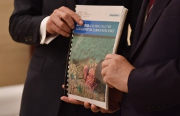 Former UN head Ban Ki-moon (R) and Patrick Verkooijen, CEO of the Global Center on Adaptation, pose with a report on climate adaptation in Beijing on September 10, 2019. - Nations rich and poor must invest now to protect against the impact of climate change -- or pay an even heavier price later, a global commission led by former UN head Ban Ki-moon warns. (Photo by GREG BAKER / AFP)