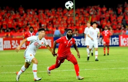 Local football legend Ali Ashfaq attempting to thwart the Chinese defence in the World Cup Qualifying match between Maldives and China on September 10. PHOTO: HUSSAIN WAHEED/MIHAARU