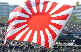 A soldier holds a Rising Sun flag during the military review at the Ground Self-Defence Force's Asaka training ground on October 27, 2013. PHOTO: GETTY IMAGES
