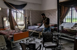 A man pictured inside a hospital allegedly hit by a regime airstrike in the town of Saraqib, northern Idlib province, on March, 2019. PHOTO: AMER ALHAMWE / AFP
