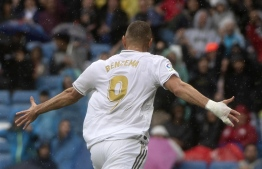 Real Madrid's French forward Karim Benzema celebrates after scoring during the Spanish league football match Real Madrid CF against Levante UD at the Santiago Bernabeu stadium in Madrid on September 14, 2019. (Photo by CURTO DE LA TORRE / AFP)