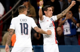 Angel Di Maria celebrates with Mauro Icardi after scoring one of his two goals as Paris Saint-Germain beat Real Madrid 3-0 in their Champions League opener. PHOTO: LUCAS BARIOULET / AFP