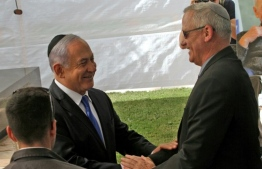 Israeli Prime Minister Benjamin Netanyahu (L) greets rival Benny Gantz, leader of Blue and White party, at a memorial ceremony for late Israeli president Shimon Peres. PHOTO: GIL COHEN-MAGEN / AFP