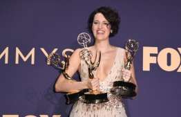 """British actress Phoebe Waller-Bridge poses with the Emmy for Outstanding Writing for a Comedy Series, Outstanding Lead Actress In A Comedy Series and Outstanding Comedy Series for """"Fleabag"""" during the 71st Emmy Awards at the Microsoft Theatre in Los Angeles on September 22, 2019. (Photo by Robyn Beck / AFP)"""