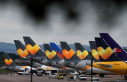 Thomas Cook logos are pictured on the tailfins of the company's passenger aircraft parked on tarmac at Manchester Airport in Manchester, northern England on September 23, 2019, after the company collapsed into bankruptcy. British travel firm Thomas Cook collapsed into bankruptcy on Monday, leaving some 600,000 holidaymakers stranded and sparking the UK's biggest repatriation since World War II. The 178-year-old operator, which had struggled against fierce online competition for some time and which had blamed Brexit uncertainty for a recent drop in bookings, was desperately seeking £200 million ($250 million, 227 million euros) from private investors to avert collapse. Oli SCARFF / AFP