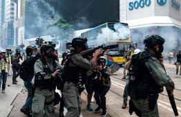 Hong Kong police fire tear gas to disperse protesters gathered in the Causeway Bay shopping district in Hong Kong on September 29, 2019. - Hong Kong descended into a second day of clashes between pro-democracy protesters and riot police on September 29 as activists step up their nearly four months campaign ahead of the 70th anniversary of communist China's founding. (Photo by Philip FONG / AFP)