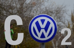 """(FILES) In this file photo taken on November 9, 2015, an activist of environmental organisation Greenpeace holds a giant letter to display """"CO2"""" around the logo of German car maker Volkswagen (VW) at the entrance of the company's headquarters in Wolfsburg, northern Germany. - Car behemoth Volkswagen will face a German court on September 30, 2019 as hundreds of thousands of owners of manipulated diesel cars demand compensation four years after the country's largest post-war industrial scandal erupted. PHOTO: JOHN MACDOUGALL / AFP"""