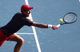Serbia's Novak Djokovic hits a return against Croatia's Mate Pavic and Brazil's Bruno Soares in their men's doubles round of 16 match at the ATP Japan Open Tennis tournament in Tokyo on September 30, 2019.  Behrouz MEHRI / AFP
