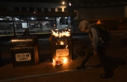 A demonstrators burns a trash bin in the street during a transport strike against the economic policies of the government of Ecuadorean President Lenin Moreno regarding the agreement signed on March with the International Monetary Fund (IMF), in Quito, on October 3, 2019. - The Ecuadorean government confirmed possible labour and tax reforms as established in the agreement, Economy Minister Richard Martinez stated -a day after announcing the elimination of fuel subsidies. (Photo by Rodrigo BUENDIA / AFP)