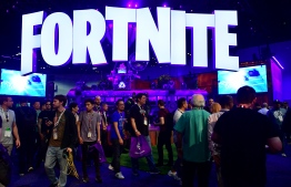 (FILES) In this file photo taken on June 12, 2018, people crowd the display area for the survival game Fortnite at the 24th Electronic Expo, or E3 2018, in Los Angeles, California. - The makers of online video gaming sensation Fortnite were accused on October 4, 2019, of designing it to be addictive, in a Canadian class action lawsuit likening playing to taking cocaine. Fortnite, released by US-based Epic Games in 2017, allows up to 100 players to fight individually or as part of a team to be the last standing on a virtual battlefield. It has become the most popular online game in the world, played by some 250 million people, including in tournaments with big cash prizes. (Photo by Frederic J. BROWN / AFP)
