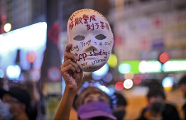 A woman holds a mask with slogans written on as protesters gather outside Mong Kok police station in Hong Kong on October 5, 2019, a day after the city's leader outlawed face coverings at protests invoking colonial-era emergency powers not used for half a century. - Masked pro-democracy protesters marched through Hong Kong in defiance of a ban on face coverings as much of the city ground to a halt on October 5, with the subway suspended and many shops shuttered following another night of violence. (Photo by Philip FONG / AFP)