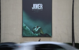 "A poster for the upcoming film ""The Joker"" is seen outside Warner Brothers Studios in Burbank, California, September 27, 2019. - The Los Angeles Police Department said Friday it plans to step up its visibility around movie theaters for the opening of ""Joker"" because of heightened fears over the film's content. (Photo by Robyn Beck / AFP)"