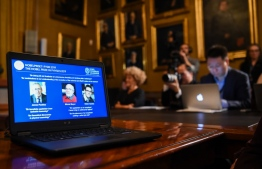 "A computer screen displays the portraits of the laureates of the 2019 Nobel Prize in Physics (L-R) Canadian-American James Peebles, Swiss scientists Michel Mayor and Didier Queloz, at the Royal Swedish Academy of Sciences on October 8, 2019 in Stockholm. - Canadian-American James Peebles, Swiss scientists Michel Mayor and Didier Queloz on October 8, 2019 won the Nobel Physics Prize for their work in cosmology, the Royal Swedish Academy of Sciences said. Peebles won one-half of the prize ""for theoretical discoveries in physical cosmology,"" while Michel Mayor and Didier Queloz shared the other half ""for the discovery of an exoplanet orbiting a solar-type star,"" professor Goran Hansson, secretary general of the academy, told a press conference. (Photo by Jonathan NACKSTRAND / AFP)"