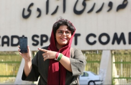 Iranian sports journalist Raha Pourbakhsh shows purchased electronic tickets for the Iran - Cambodia World Cup 2022 qualifier match during an interview with AFP in front of Azadi stadium in the capital Tehran on October 8, 2019. - After a ban spanning decades, Iranian women are set to freely enter a football stadium for the first time on October 10 as Iran hosts Cambodia in a World Cup 2022 qualifier at Tehran's Azadi stadium. (Photo by ATTA KENARE / AFP)