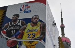 "A worker removes a promotional banner from a building for the National Basketball Association (NBA) October 10 preseason game in China between the Brooklyn Nets and the Los Angeles Lakers in Shanghai on October 9, 2019. - Chinese state media slammed the NBA for an ""about-face"" on October 9 after the body said it would not apologise for a tweet by the Houston Rockets General Manager supporting pro-democracy protests in Hong Kong. (Photo by HECTOR RETAMAL / AFP)"