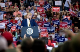 """US President Donald Trump looks on during a """"Keep America Great"""" rally at Sudduth Coliseum at the Lake Charles Civic Center in Lake Charles, Louisiana, on October 11, 2019. (Photo by SAUL LOEB / AFP)"""