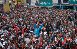 Kenyans watch a big screen on October 12, 2019, in Nairobi as they celebrate Kenya's Eliud Kipchoge victory. - Kenya's Eliud Kipchoge, on October 12, 2019, made history, busting the mythical two-hour barrier for the marathon on a specially prepared course in a huge Vienna park. With an unofficial time of 1hr 59min 40.2sec, the Olympic champion became the first ever to run a marathon in under two hours in the Prater park with the course readied to make it as even as possible. (Photo by Yasuyoshi CHIBA / AFP)