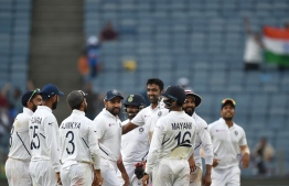 Indian cricket players stand in huddle as they celebrate after the wicket of South Africa's batsman Keshav Maharaj during the third day of play of the second test cricket match between India and South Africa, at the Maharashtra Cricket Association Stadium in Pune on October 12, 2019. (Photo by PUNIT PARANJPE / AFP) /