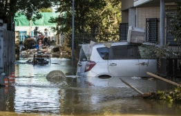 Flooded vehicles are seen in the aftermath of Typhoon Hagibis in Kawasaki on October 13, 2019. - Japan's military scrambled October 13 to rescue people trapped by flooding in the aftermath of powerful Typhoon Hagibis, which killed at least four people, caused landslides and burst rivers. (Photo by Odd ANDERSEN / AFP)