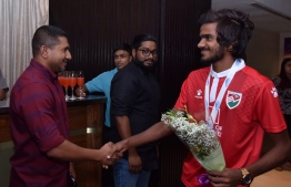 Minister of Youth, Sports and Community Development Ahmed Mahloof (L) and an athlete of the Under-18 National Football Team. PHOTO: FOOTBALL ASSOCIATION OF MALDIVES