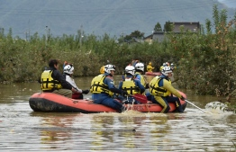 Emergency personnel paddle across floodwaters using an inflatable raft during search and rescue operations in the aftermath of Typhoon Hagibis, in Nagano on October 14, 2019. - Tens of thousands of rescue workers were searching October 14 for survivors of powerful Typhoon Hagibis, two days after the storm slammed into Japan, killing at least 35 people. (Photo by Kazuhiro NOGI / AFP)
