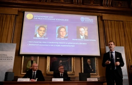 """Peter Fredriksson (L), chairman of the Economic Sciences Prize Committee 2019, and the Royal Swedish Academy of Sciences' secretary general Goran Hansson (2nd L) listen to Jakob Svensson (R), member of the Economic Sciences Prize Committee 2019, as he explains the field of work of the co-winners of the 2019 Sveriges Riksbank Prize in Economic Sciences in Memory of Alfred Nobel (on the screen, L-R: Abhijit Banerjee, Esther Duflo and Michael Kremer) during a press conference at the Royal Swedish Academy of Sciences in Stockholm, Sweden, on October 14, 2019. Indian-born Abhijit Banerjee of the US, French-American Esther Duflo and Michael Kremer of the US won the Nobel Economics Prize for their """"experimental approach to alleviating global poverty"""", the Royal Swedish Academy of Sciences said. Jonathan NACKSTRAND / AFP"""