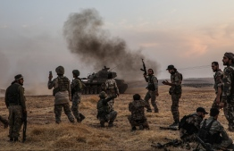 (FILES) In this file photo taken on October 14, 2019 Turkish soldiers and Turkey-backed Syrian fighters gather on the northern outskirts of the Syrian city of Manbij near the Turkish border as Turkey and its allies continue their assault on Kurdish-held border towns in northeastern Syria. (Photo by Zein Al RIFAI / AFP)
