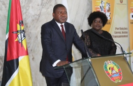 Mozambican President Felipe Nyusi(L) speaks as his wife Isaura(R) listens after casting their ballots at the Jozina Machel school during the Mozambican General Elections on October 15, 2019 in Maputo, Mozambique. (Photo by Robert Paquete / AFP)