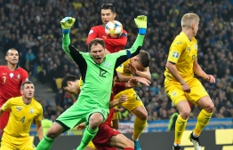 Ukraine's goalkeeper Andriy Pyatov and Portugal's forward Cristiano Ronaldo in action during the Euro 2020 football qualification match between Ukraine and Portugal at the NSK Olimpiyskyi stadium in Kiev on October 14, 2019. (Photo by GENYA SAVILOV / AFP)