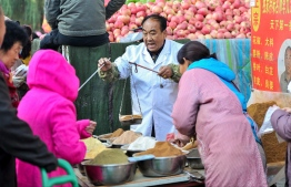 This photo taken on October 15, 2019 shows a vendor (C) selling spices at a market in Shenyang in China's northeastern Liaoning province. - China's economy expanded at its slowest rate in nearly three decades during the third quarter 2019, held back by cooling domestic demand and a protracted US trade war, according to an AFP survey of analysts on October 16. (Photo by STR / AFP) /