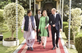 Pakistan's Prime Minister Imran Khan (L) walks with Britain's Prince William (R), Duke of Cambridge, and his wife Catherine (C), Duchess of Cambridge, at the Prime Minister House in Islamabad on October 15, 2019. - Pakistani Prime Minister Imran Khan gave a warm welcome in Islamabad on October 15 to Britain's Prince William, the son of his late friend Princess Diana, who is on his first official trip to the country with his wife Kate. (Photo by STR / AFP)