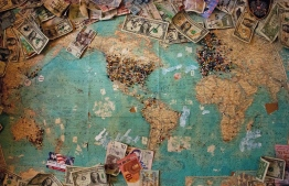 Foreign currency notes on a world map. PHOTO: CHRISTINE ROY / UNSPLASH