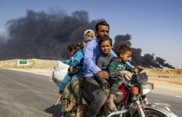 """Displaced people, fleeing from the countryside of the Syrian Kurdish town of Ras al-Ain along the border with Turkey, ride a motorcycle together along a road on the outskirts of the nearby town of Tal Tamr on October 16, 2019 as they flee from the Turkish """"Peace Spring"""" military operation, with smoke plumes of tire fires billowing in the background to decrease visibility for Turkish warplanes in the area. (Photo by Delil SOULEIMAN / AFP)"""