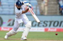 India's captain Virat Kohli plays a shot on the second day of the second Test cricket match between India and South Africa at the Maharashtra Cricket Association Stadium in Pune on October 11, 2019. (Photo by PUNIT PARANJPE / AFP) /