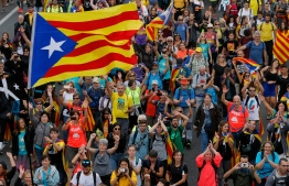 Pro independence protesters march in San Vicenc dels Horts, on October 18, 2019, on the day that separatists have called a general strike and a mass rally. - Catalan separatists burned barricades and clashed with police in Barcelona yesterday in a fourth night of violence triggered by Spain's jailing of nine of their leaders over a failed independence bid while today they have blocked traffic on two routes connecting Spain and France, on the fifth day of protests, the transport ministry said Friday. (Photo by Pau Barrena / AFP)