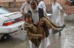"""A volunteer carries an injured youth to hospital, following a bomb blast in Haska Mina district of Nangarhar Province on October 18, 2019. - At least 28 worshippers were killed and dozens wounded by a blast inside an Afghan mosque during Friday prayers on October 18, officials said, a day after the United Nations said violence in the country had reached """"unacceptable"""" levels. (Photo by NOORULLAH SHIRZADA / AFP)"""