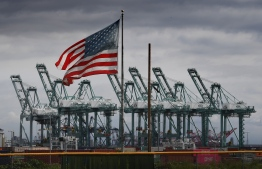 """(FILES) In this file photo taken on March 04, 2019 the US flag flies over shipping cranes and containers after a report said the United States and China are close to reaching a major trade deal that would see both sides lower some of the tariffs imposed during an often-bitter trade war, in Long Beach, California. - President Donald Trump on October 11, 2019, hailed breakthrough in his drawn-out trade war with China, saying the two sides had reached an initial deal. At the White House, Trump told reporters the two sides had """"come to a very substantial phase one deal."""" (Photo by Mark RALSTON / AFP)"""