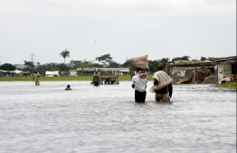 People carry their belonging on their heads while they walk on a  flooded road following heavy rain downpour in Wawa in Ogun State southwest Nigeria, on October 15, 2019. - Residents of Wawa community in Ogun State, and neighbouring states in southwest Nigeria are still suffering from the wreaked havoc following a downpour that left many homes and offices flooded, roads impassable and disrupted economic activities across the states. (Photo by PIUS UTOMI EKPEI / AFP)