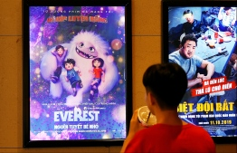 """A boy looks at a poster for the animated movie """"Everest Nguoi Tuyet Be Nho"""", also known as """"Abominable"""", at a movie theatre in Hanoi on October 14, 2019. - Vietnam has pulled the animated film """"Abominable"""" from theatres over a scene featuring a map of the South China Sea showing Beijing's claims in the flashpoint waterway, state media reported on October 14. (Photo by Nhac NGUYEN / AFP)"""