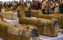 Tourists photograph sarcophagi displayed in front of Hatshepsut Temple in Egypt's valley of the Kings in Luxor on October 19, 2019. - Egypt revealed today a rare trove of 30 ancient wooden coffins that have been well-preserved over millennia in the archaeologically rich Valley of the Kings in Luxor. The antiquities ministry officially unveiled the discovery made at Asasif, a necropolis on the west bank of the Nile River, at a press conference against the backdrop of the Hatshepsut Temple. (Photo by Khaled DESOUKI / AFP)